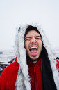 Portrait of young man with fur hood  pulling a face in the snow - INGF05207