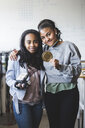 Portrait of successful female students holding robot and gold medal while standing in classroom at high school - MASF09289