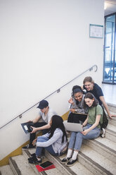 Full length of happy multi-ethnic students talking and sitting on steps at high school - MASF09304