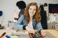 Portrait of smiling redhead female technician sitting at workbench while colleagues working in creative office - MASF09325
