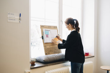 Confident businesswoman writing strategy on placard over window sill at creative office - MASF09343