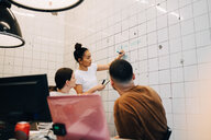 Young businesswoman brainstorming colleagues while writing strategy on tile wall at creative office - MASF09409