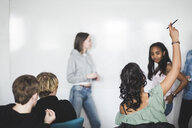 Teenage sitting with hand raised by friends in classroom at high school - MASF09463