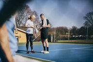 Senior man and woman with rackets talking while standing at tennis court - MASF09478