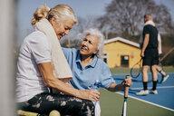 Senior woman talking to tired friend at tennis court - MASF09481