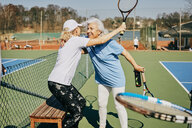 Happy female senior friends greeting at tennis court during summer - MASF09487