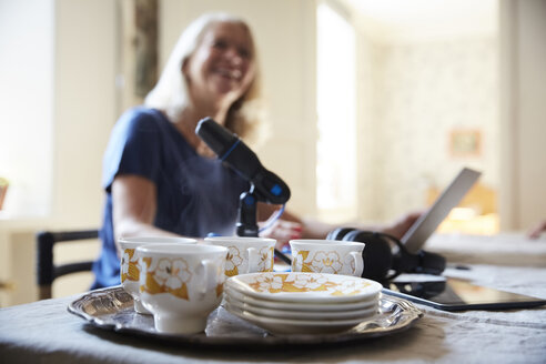 Close-up of crockery and microphone with woman sitting in background at home - MASF09511