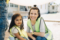 Portrait of smiling female teacher with student in playground against school building - MASF09520