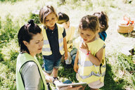 High angle view of female teacher sharing digital tablet to students in playground - MASF09523