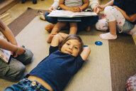 High angle portrait of boy lying on carpet amidst friends in classroom - MASF09547