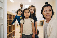 Teacher and students looking away in classroom at child care - MASF09562