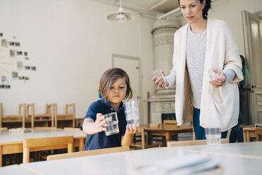 Mid adult teacher with boy arranging drinking glasses on table in classroom at child care - MASF09565