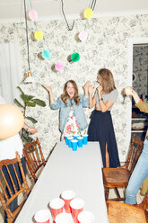 Surprised young woman playing beer pong with friends during dinner party at home - MASF09595