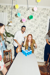 Confident young woman playing beer pong on table by male friend at dinner party - MASF09598