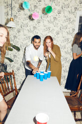 Confident young man playing beer pong on table by female friend at dinner party - MASF09601