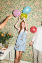 Young man with balloons standing by man against wallpaper during dinner party at home - MASF09616