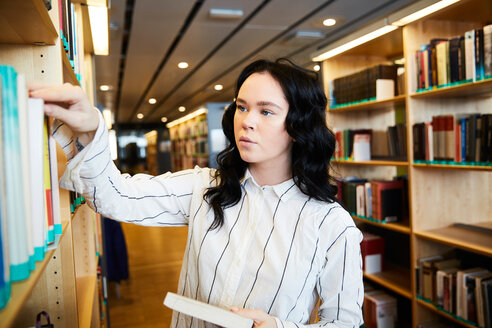 Young female student searching book in university library - MASF09661