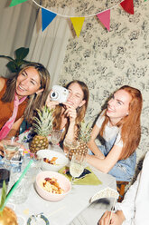 Tilt shot of young woman sitting with camera amidst multi-ethnic friends at dining table during party in apartment - MASF09685