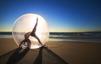 Woman doing yoga in ball on beach during sunset - LUXF02103