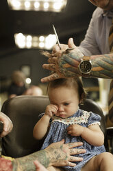 Cropped image of barber cutting baby girl's hair at salon - TGBF00318