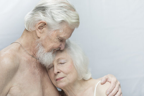 Close-up of relaxed senior couple with arms around against gray background - TGBF00333