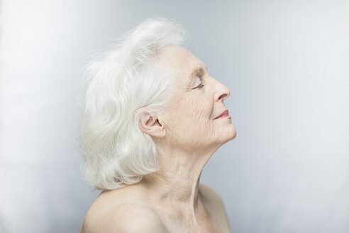 Close-up side view of relaxed senior woman with eyes closed against gray background - TGBF00336