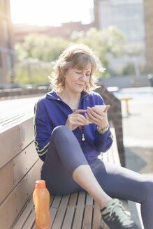 Active senior woman using mobile phone after workout in city on sunny day - TGBF00378