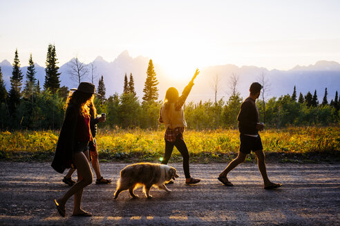 Friends with dog walking on road at dusk in  Grand Teton National Park - TGBF00420