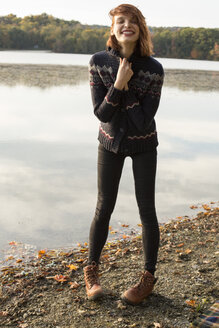 Full length portrait of happy young woman wearing sweater while standing by lake - TGBF00465