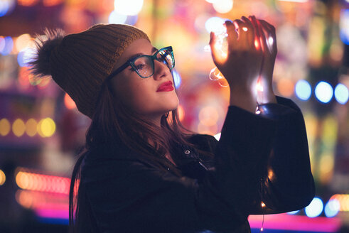 Close-up of a young woman holding illuminated lights - INGF05260