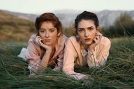 Portrait of young women sitting in a grassy field - INGF05374