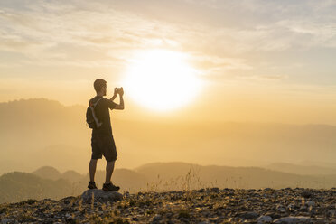 Spain, Barcelona, Natural Park of Sant Llorenc, man hiking and taking a picture of the view at sunset - AFVF01889