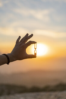 Close-up of man's hand holding an hourglass at sunset - AFVF01898