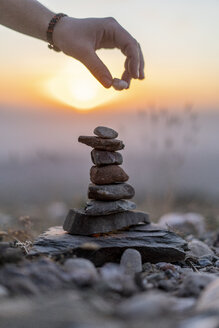 Close-up of man's hand placing stone on cairn at sunset - AFVF01904
