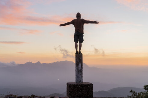 Spain, Barcelona, Natural Park of Sant Llorenc, man standing on pole at sunset - AFVF01907