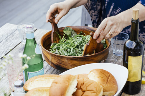 Midsection of woman tossing salad leaves in wooden bowl at table - TGBF00489
