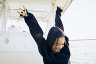 Smiling girl wearing hoody on boat - TGBF00534