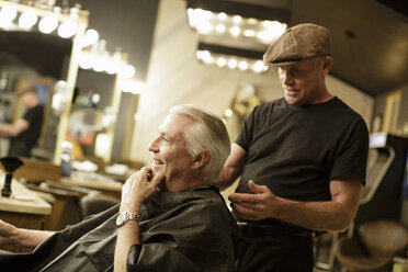 Side view of happy senior man receiving haircut from barber at shop - TGBF00570