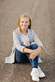 Portrait of smiling girl sitting on ground - NMSF00275