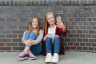 Portrait of two smiling girls sitting in front of brick wall taking selfie with smartphone - NMSF00284