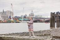 UK, London, happy girl taking selfie in front of River Thames - XCF00180