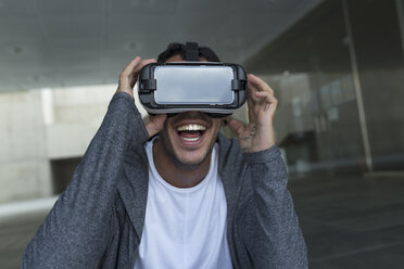 Excited young man wearing Virtual Reality Glasses - JPTF00051