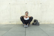Tattooed young man with roller skates sitting on ground having fun - JPTF00054