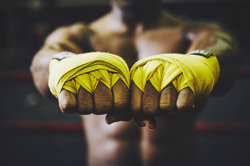 Midsection of boxer showing hands wrapped with bandages at health club - TGBF00643