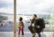 Father and daughter with backpacks at the airport looking at the planes - GEMF02433