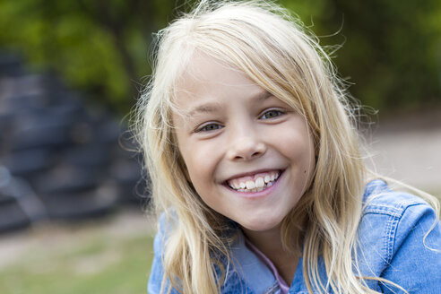 Portrait of smiling blond girl outdoors - JFEF00905