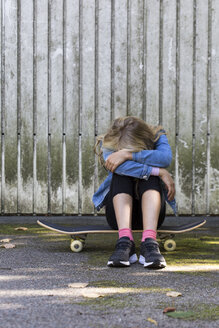 Girl sitting on her skateboard outdoors hiding her face - JFEF00908