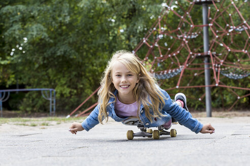 Portrait of smiling blond girl with skateboard on a playground - JFEF00911