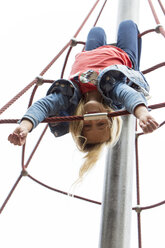 Blond girl hanging upside down on jungle gym at playground - JFEF00914