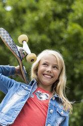 Portrait of happy blond girl with skateboard on her shoulder - JFEF00917